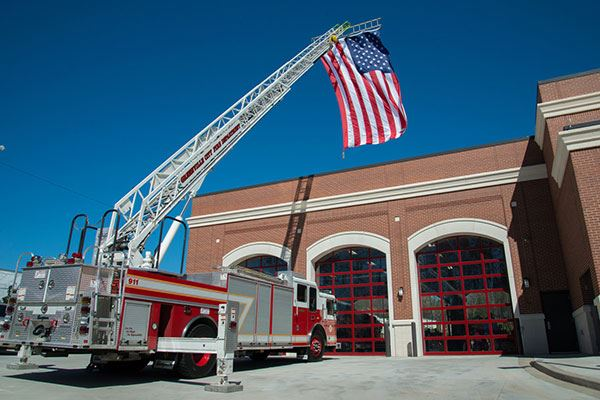Flag hanging from firetruck, over the newly opened Station 1