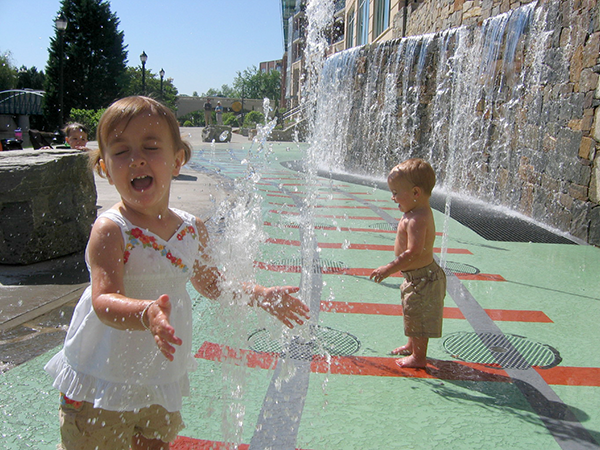 Children playing in the railroad-themed splash fountain at Riverplace